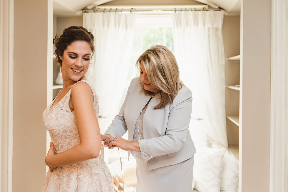 mother tying up daughters wedding dress before wedding ceremony at La Paletta Mansion in Burlington Ontario