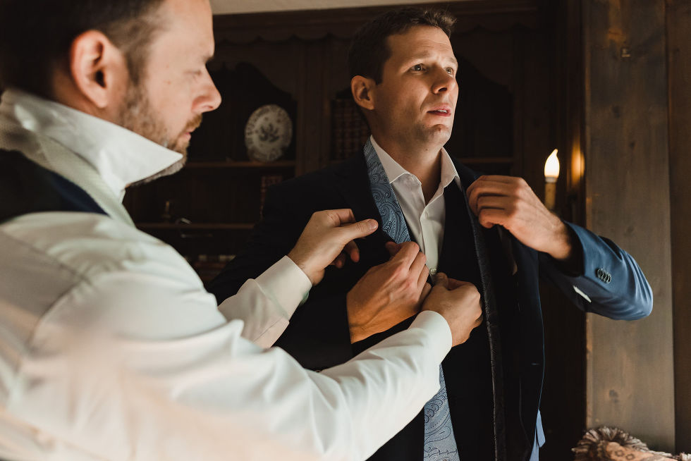 groomsman in white dress shirt helping groom put on his light blue tie over navy suit before wedding at La Paletta Mansion in Burlington Ontario