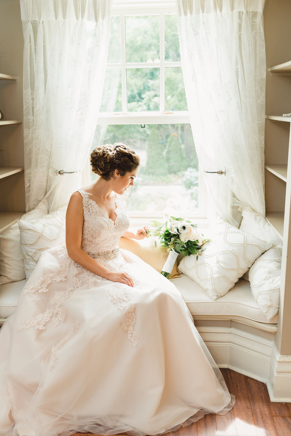 bride sitting in windowsill and gazing down at her floral bouquet as she waits for her wedding ceremony at La Paletta Mansion in Burlington Ontario