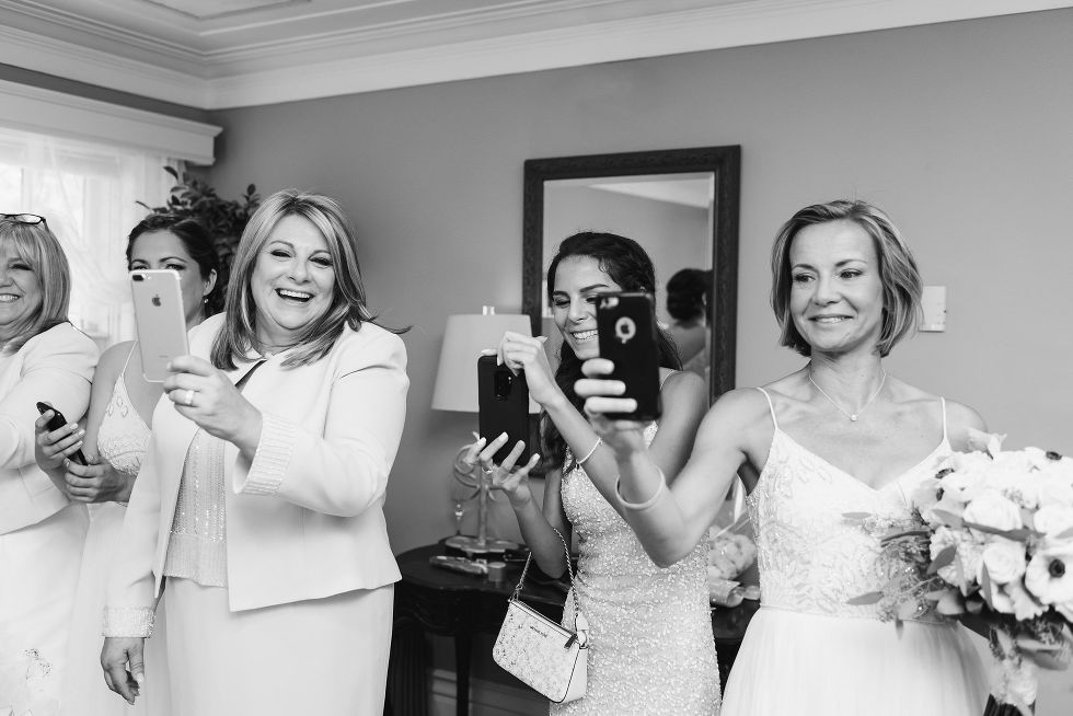 mother of the bride and bridesmaids taking pictures with their phones before wedding at La Paletta Mansion in Burlington Ontario