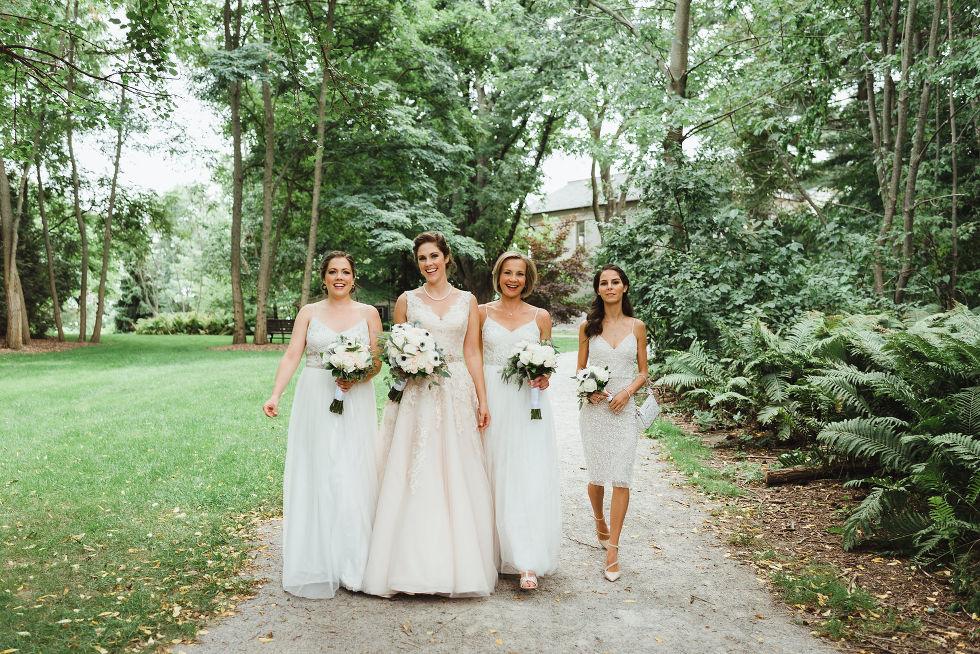 bride strolling through gardens with her 3 bridesmaids before her wedding at La Paletta Mansion in Burlington Ontario