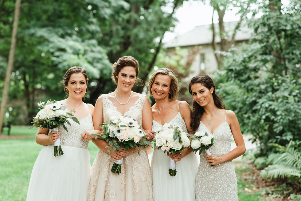 bride and her 3 bridesmaids all holding white floral bouquets in the gardens at La Paletta Mansion in Burlington Ontario