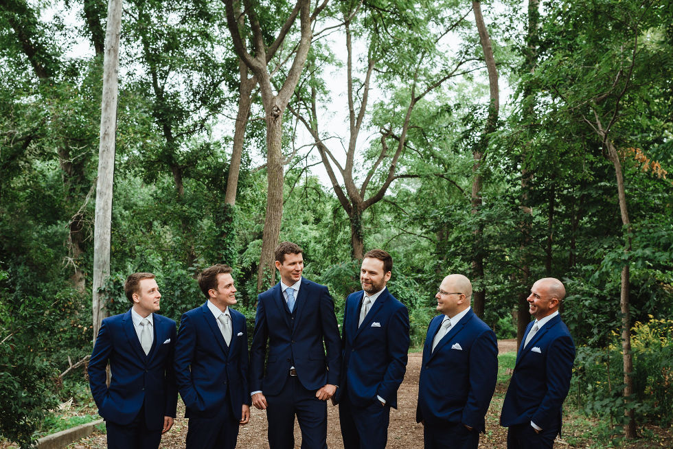groom and his 5 groomsmen standing in blue suits in the gardens before wedding ceremony at La Paletta Mansion in Burlington Ontario