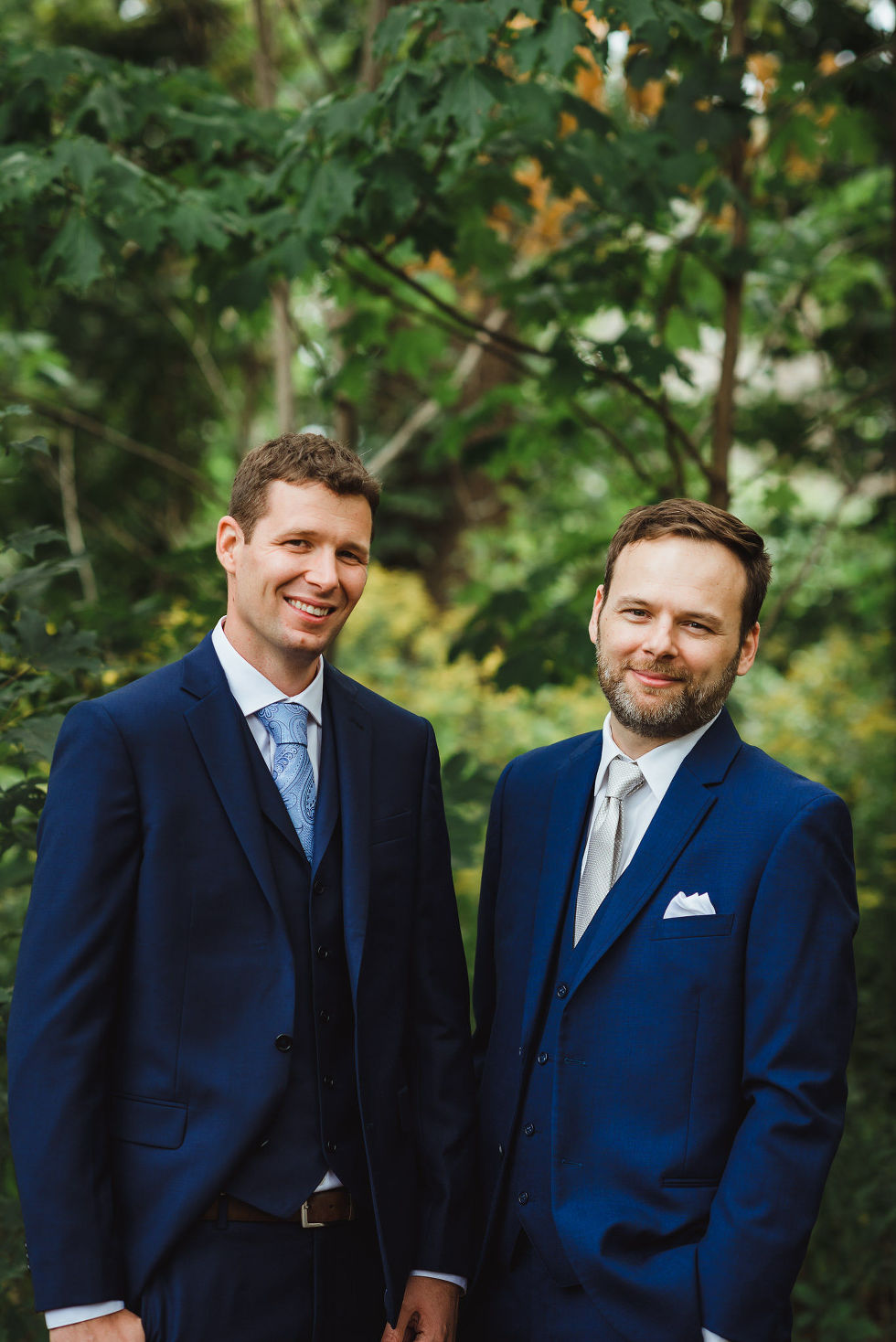 groom and best man standing next to each other in blue suits in the gardens of La Paletta Mansion in Burlington Ontario
