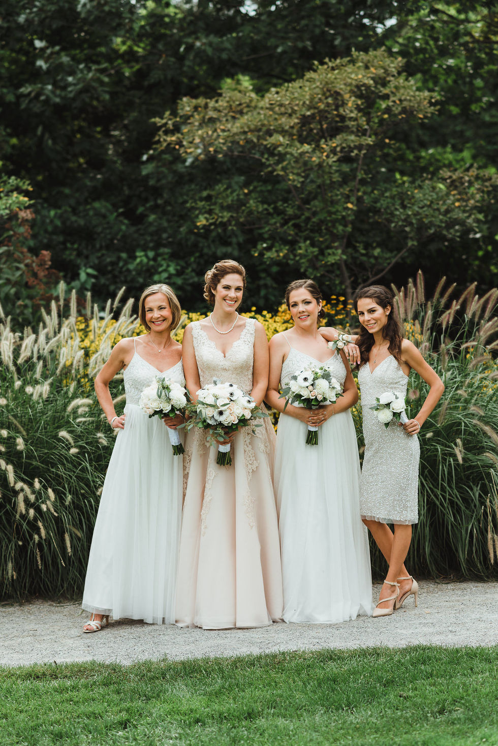 bride and her bridesmaids standing in front of a garden before the wedding ceremony at La Paletta Mansion in Burlington Ontario