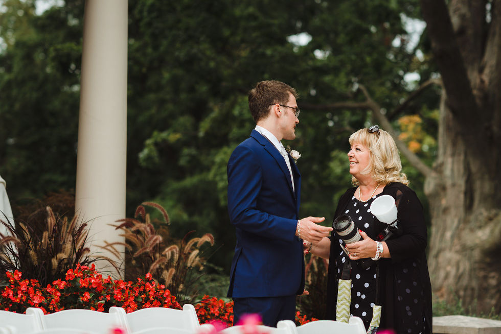 groomsman in a blue suit greeting a wedding guest before the ceremony at La Paletta Mansion in Burlington Ontario