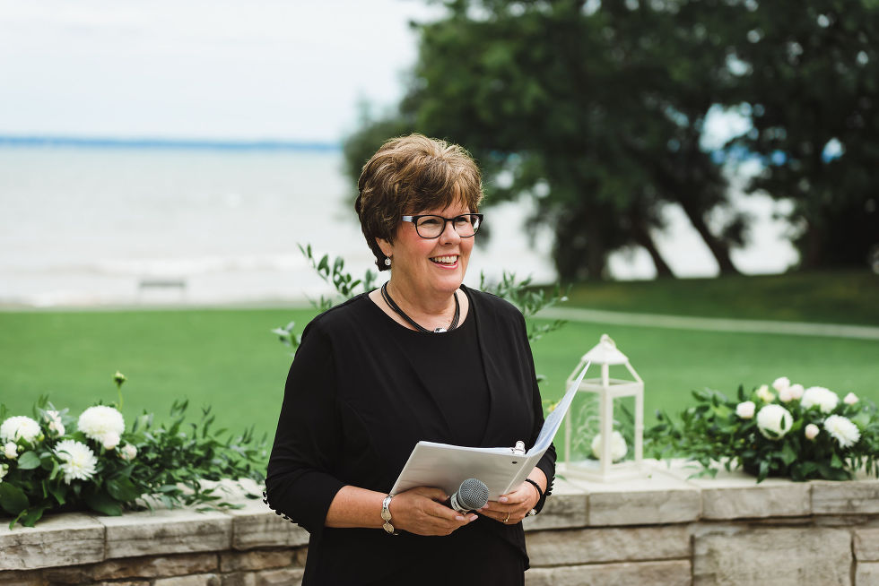 Officiant standing in front of Lake Ontario holding microphone and book as she awaits the arrival of bride and groom for ceremony at La Paletta Mansion in Burlington Ontario