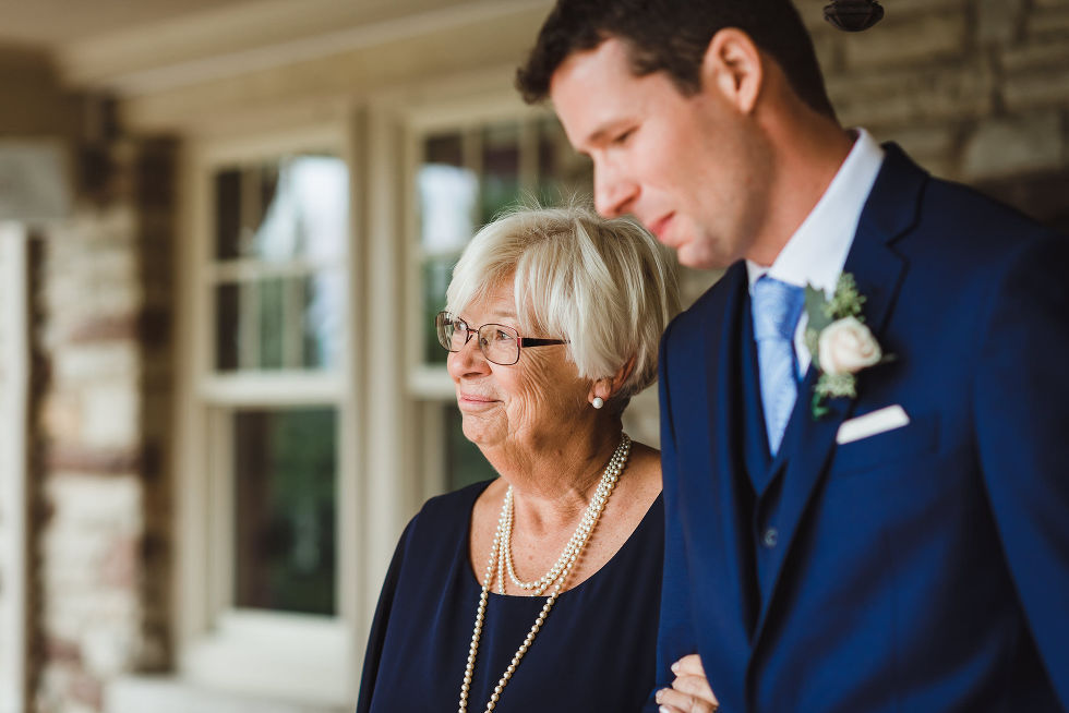 mother of the groom walking her son out before the beginning of the no first look wedding ceremony at La Paletta Mansion in Burlington Ontario