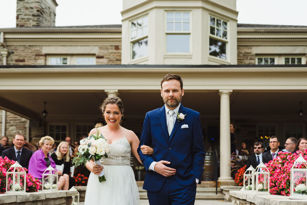 groomsman and bridesmaid walk down aisle together as wedding guests look on during no first look wedding ceremony at La Paletta Mansion in Burlington Ontario