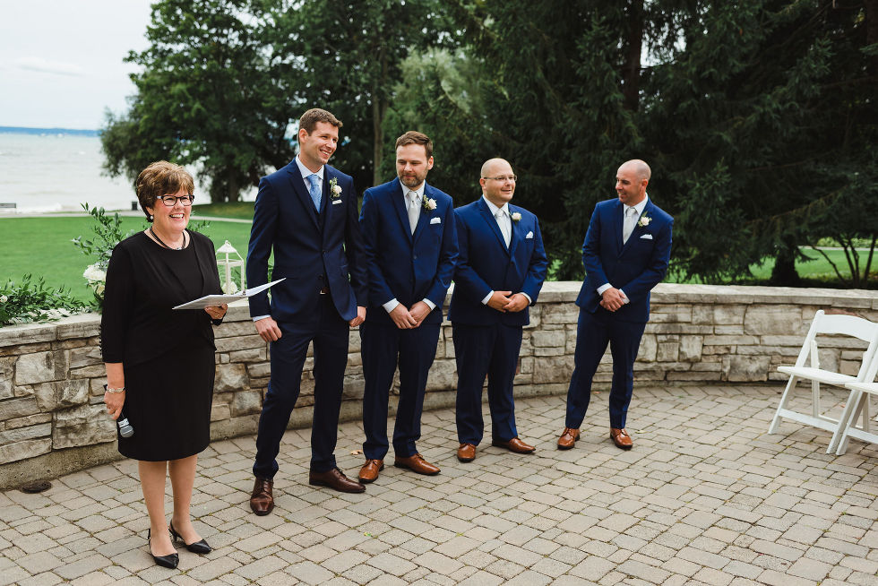 groom stands in front of Lake Ontario alongside his 3 groomsmen and the officiant on the other side as he awaits his bride to enter the ceremony at La Paletta Mansion in Burlington Ontario