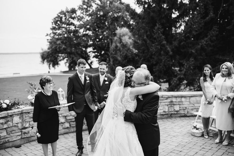 father of the bride hugs his daughter with groom, groomsmen, officiant, and Lake Ontario in the background at La Paletta Mansion in Burlington Ontario