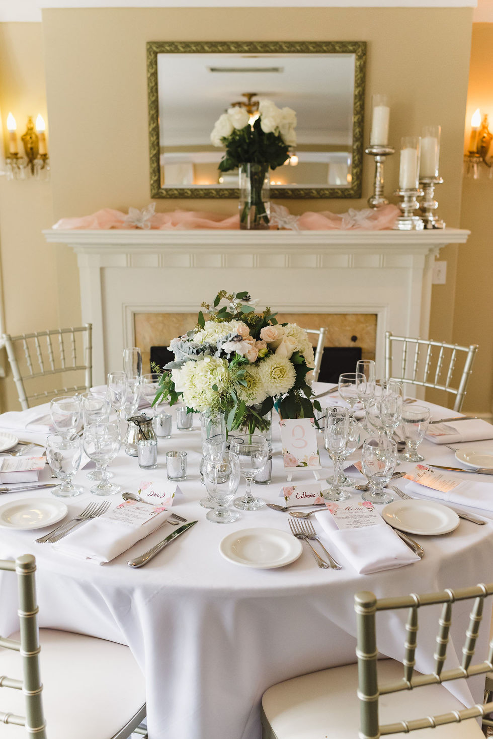 table set with plates, cutlery, and floral bouquet in front of a decorated mantle for a wedding at La Paletta Mansion in Burlington Ontario