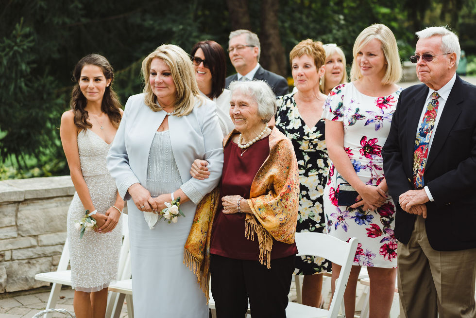 wedding guests look on with smiles during no first look wedding ceremony at La Paletta Mansion in Burlington Ontario