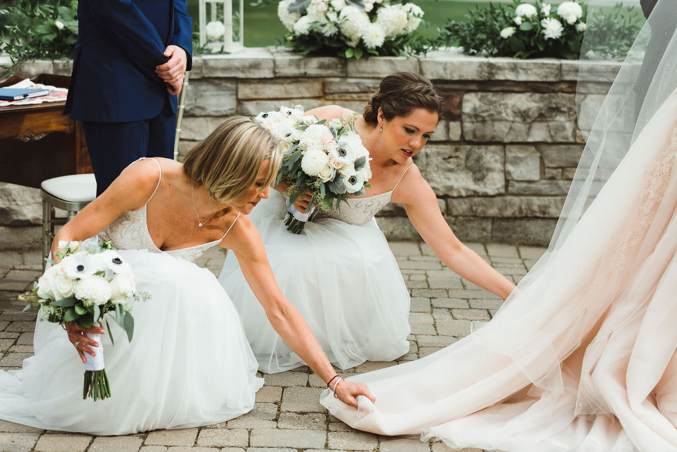 2 bridesmaids holding white floral bouquets and crouched down to hold up bottom of the brides wedding dress during no first look wedding at La Paletta Mansion