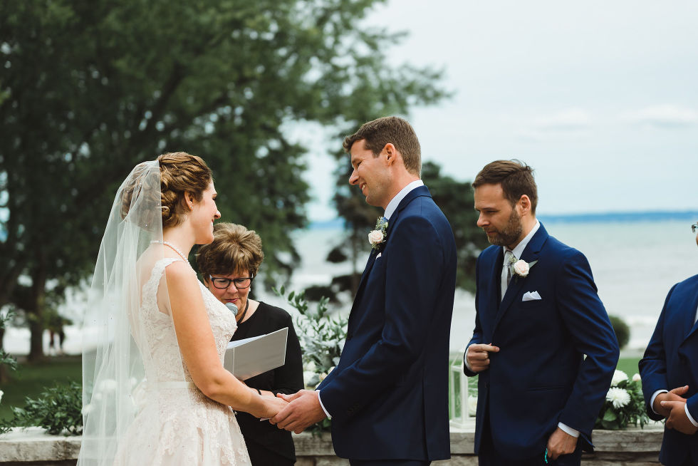 bride and groom stand before officiant with Lake Ontario in the background during their no first look wedding ceremony at La Paletta Mansion in Burlington Ontario