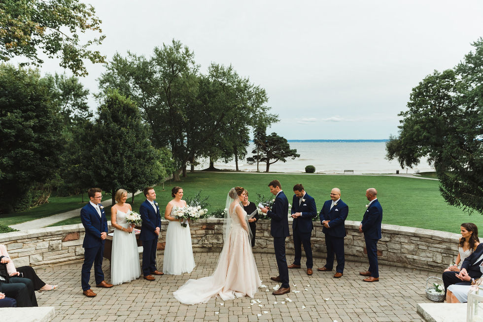 bride and groom stand before officiant and wedding party with Lake Ontario in the background during their no first look wedding ceremony at La Paletta Mansion in Burlington Ontario