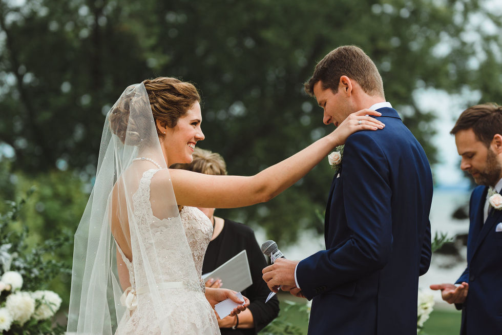 bride resting her hand on grooms shoulder as he reads vows into microphone