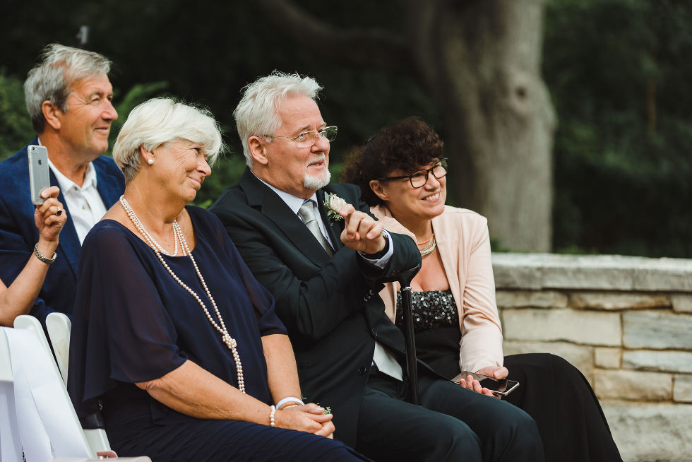 4 wedding guests smiling as they watch no first look wedding ceremony at La Paletta Mansion in Burlington Ontario