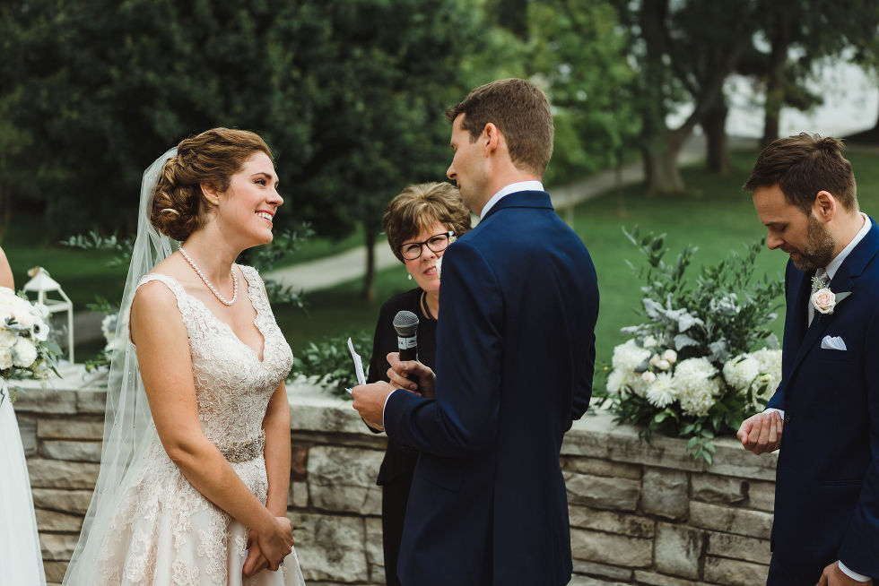 bride smiling at her groom as he reads vows into microphone during no first look wedding ceremony at La Paletta Mansion in Burlington Ontario