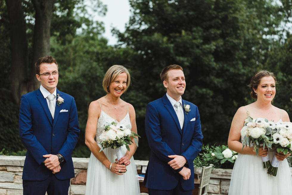 wedding party smiling as they watch the no first look wedding ceremony at La Paletta Mansion in Burlington Ontario