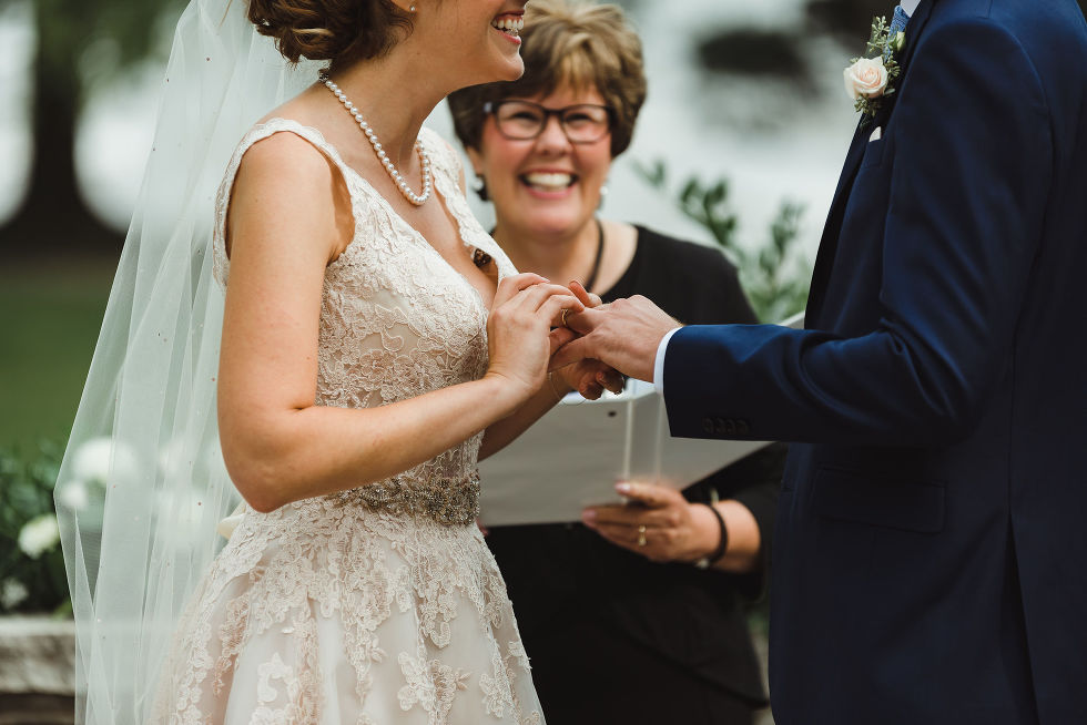 bride smiling as she places wedding band on groom during their no first look ceremony at La Paletta Mansion