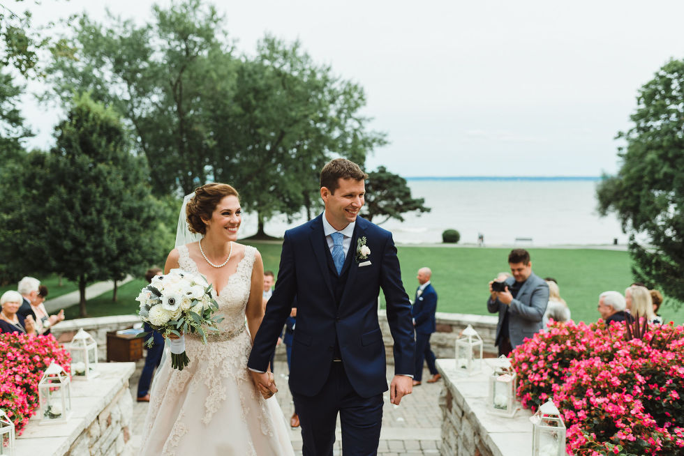 bride and groom smiling and holding hands as they exit wedding ceremony with Lake Ontario in the background at La Paletta Mansion in Burlington Ontario