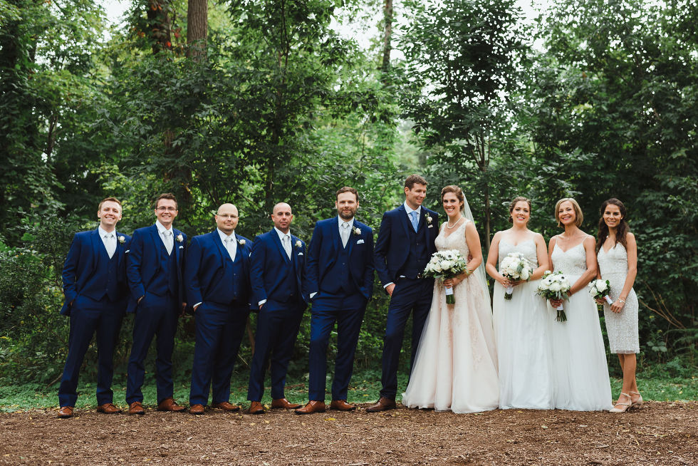 bride and groom stand between their wedding party in a forest after their no first look wedding ceremony at La Paletta Mansion in Burlington Ontario