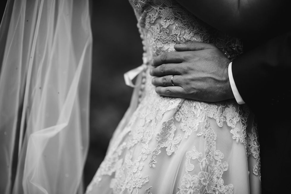 grooms hand on the back of his brides wedding dress after no first look wedding ceremony at La Paletta Mansion in Burlington Ontario