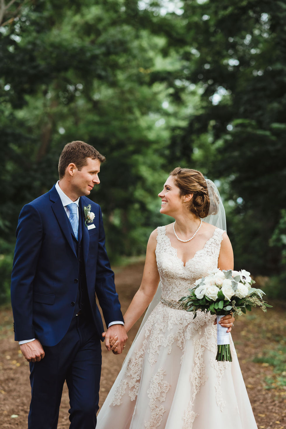 bride and groom holding hands and looking at each other with smiles after no first look wedding ceremony at La Paletta Mansion in Burlington Ontario