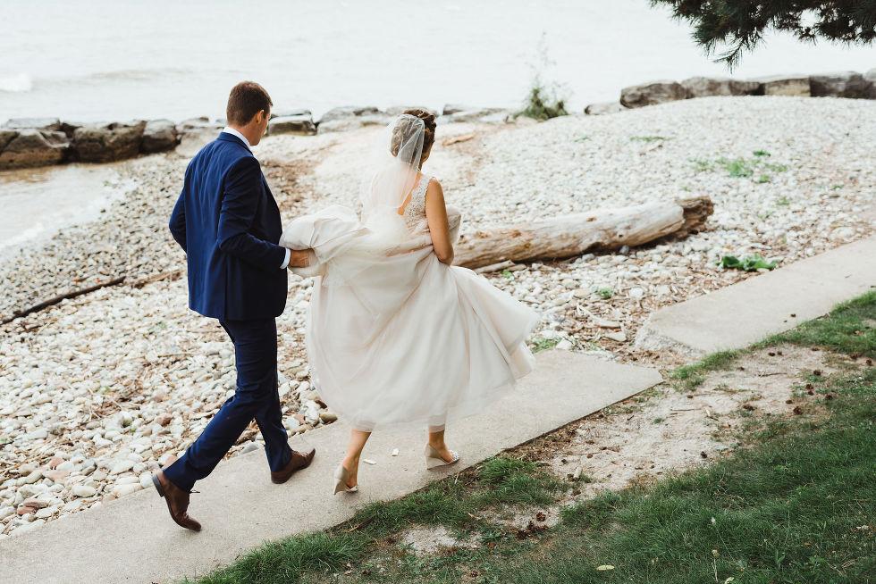 bride and groom walk alongside Lake Ontario after no first look wedding ceremony at La Paletta Mansion in Burlington Ontario
