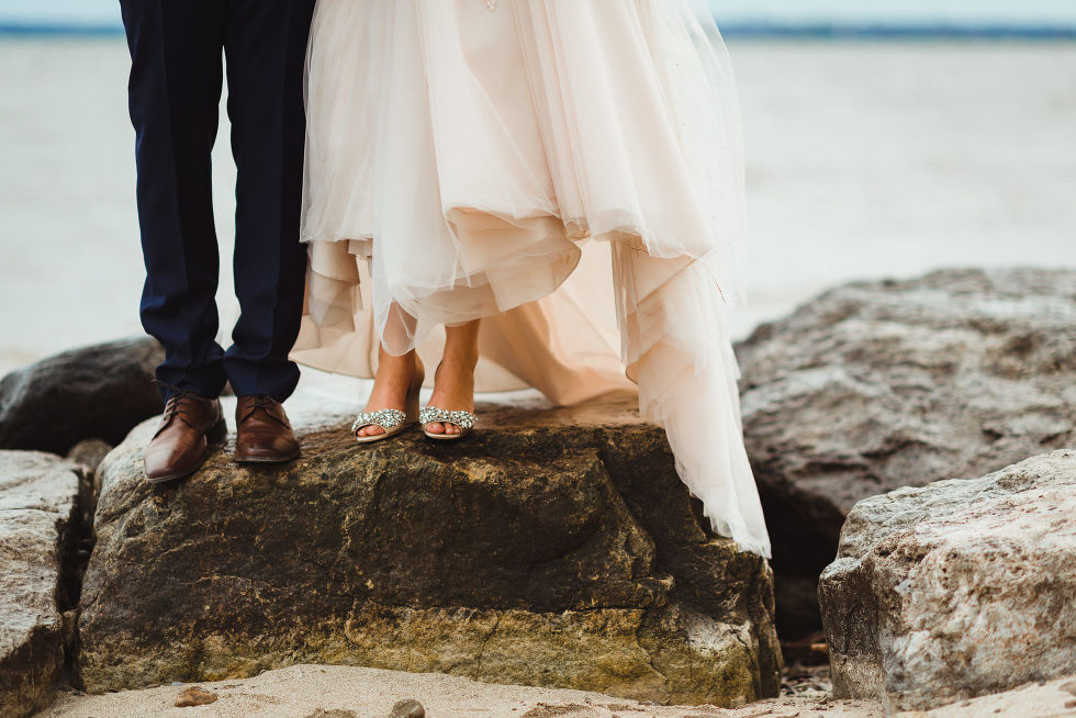 bride and groom standing on the rock shoreline of Lake Ontario after no first look wedding ceremony at La Paletta Mansion in Burlington Ontario