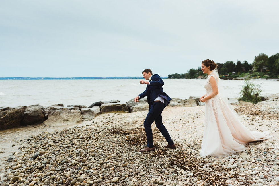 bride watching her groom skipping a rock on the shoreline of Lake Ontario after no first look wedding ceremony at La Paletta Mansion in Burlington Ontario