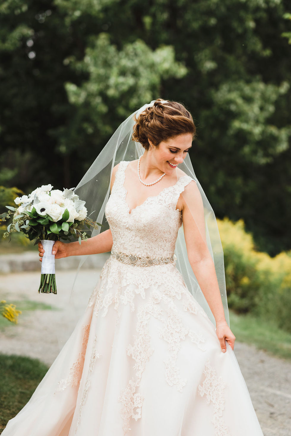 bride pulling at the side of her wedding dress and holding a white floral bouquet in the other hand after no first look wedding ceremony at La Paletta Mansion in Burlington Ontario