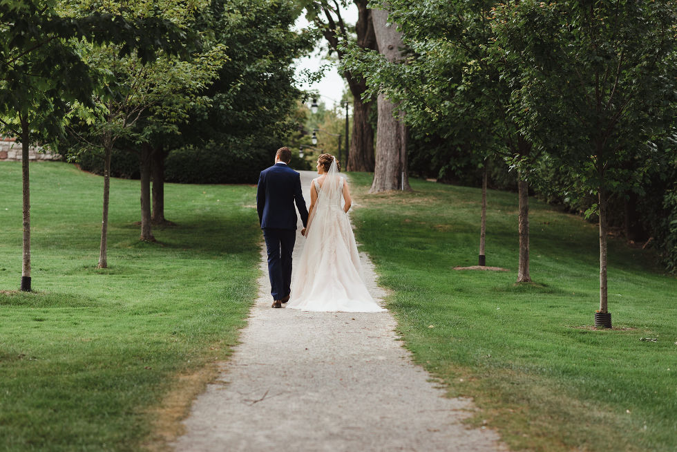 bride and groom holding hands and strolling the ground of La Paletta Mansion in Burlington Ontario after their no first look wedding ceremony