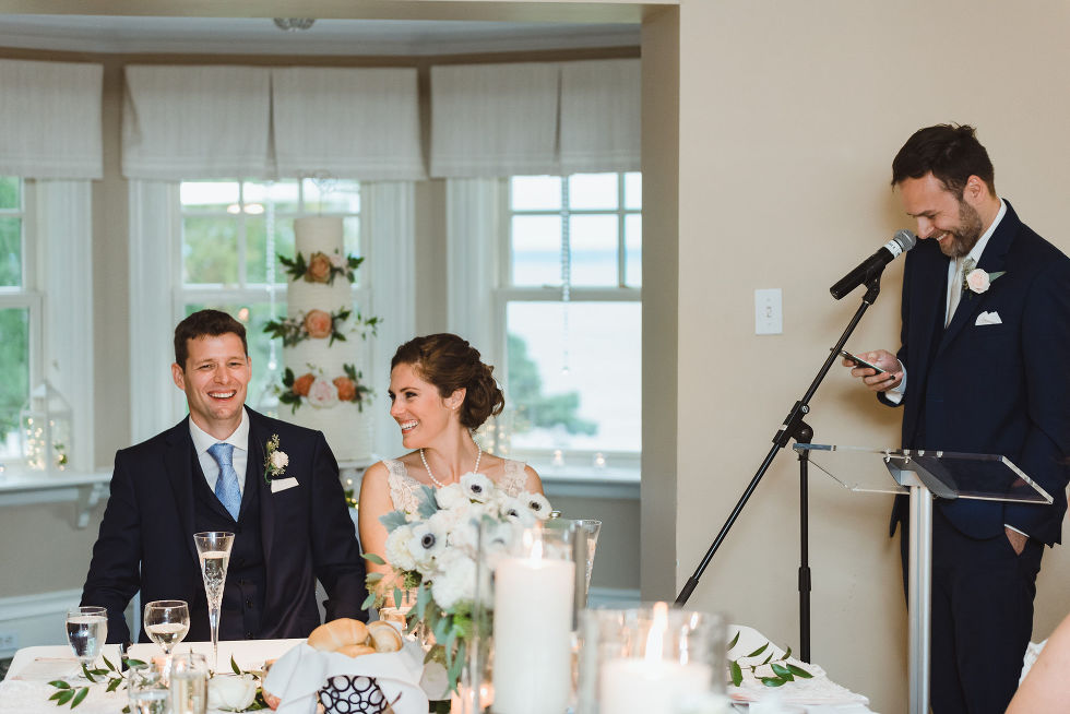 bride and groom smiling as they listen to best man read a speech from his phone during reception after no first look wedding ceremony at La Paletta Mansion in Burlington Ontario