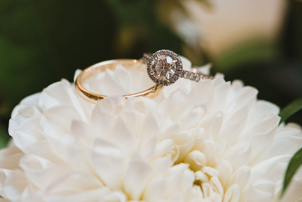diamond wedding ring and gold wedding band rest on a white flower during no first look wedding ceremony at La Paletta Mansion in Burlington Ontario