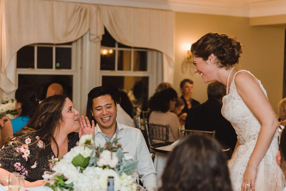 bride laughing as she speaks with a couple of wedding guests seated at their table during reception at La Paletta Mansion in Burlington Ontario