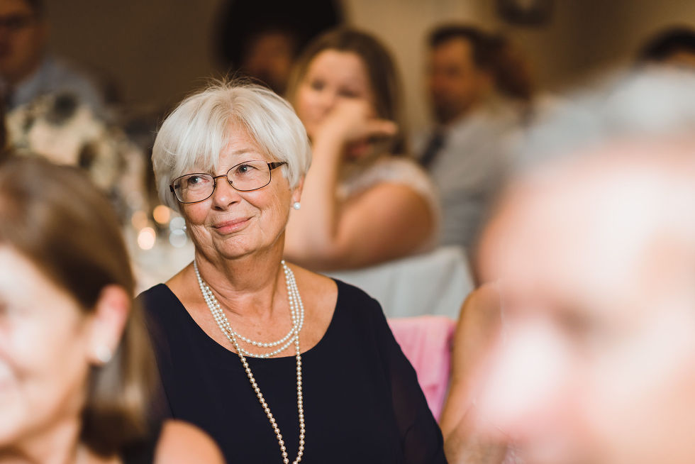 mother of the groom listening to the wedding speeches during her sons no first look wedding at La Paletta Mansion in Burlington Ontario