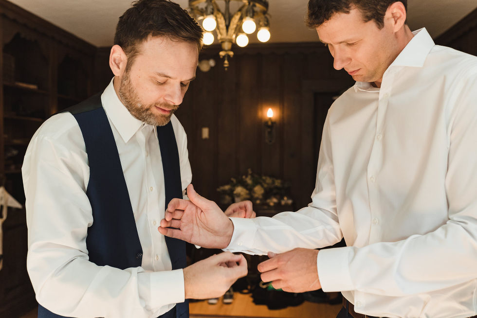groomsman in white shirt and blue vest helping groom attach his cufflinks on dress shirt before wedding at La Paletta Mansion in Burlington Ontario