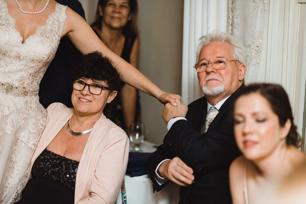 bride holding the hand of a seated male guest during her wedding reception at La Paletta Mansion in Burlington Ontario