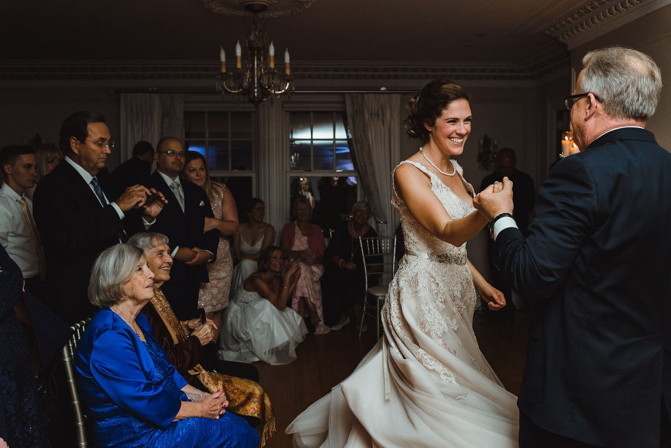 father of the bride sharing a first dance with the smiling bride during wedding reception at La Paletta Mansion in Burlington Ontario