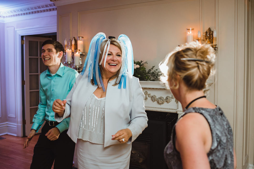 woman wearing a blue and white wig dancing with a couple other wedding guests during the reception at La Paletta Mansion in Burlington Ontario