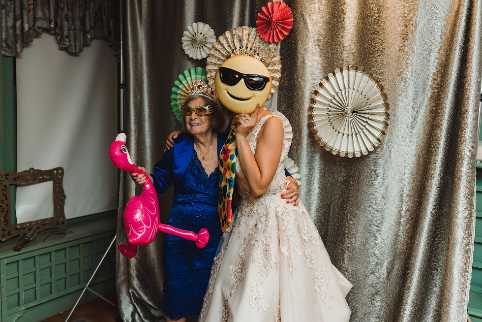 bride and a wedding guest posing for pictures with wacky props and masks during no first look wedding at La Paletta Mansion in Burlington Ontario
