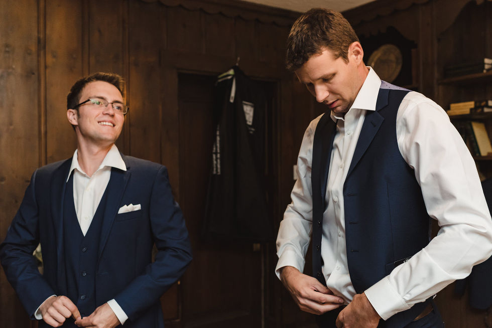groom and one of his groomsmen finish dressing in blue suits before wedding at La Paletta Mansion in Burlington Ontario
