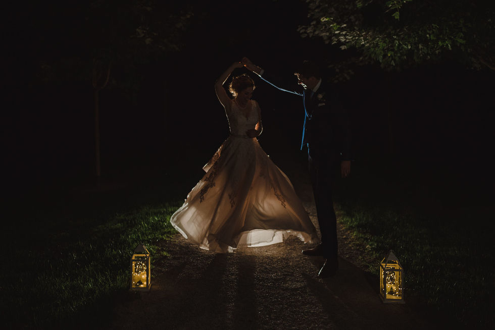 silhouette of bride being twirled by her groom with lanterns at their feet after their no first look wedding at La Paletta Mansion in Burlington Ontario