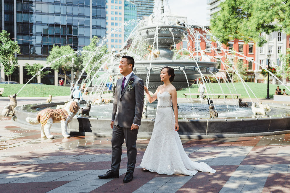 bride approaches groom for first look at the dog fountain in Berzcy Park, before their Parisian inspired wedding at La Maquette in Toronto Ontario