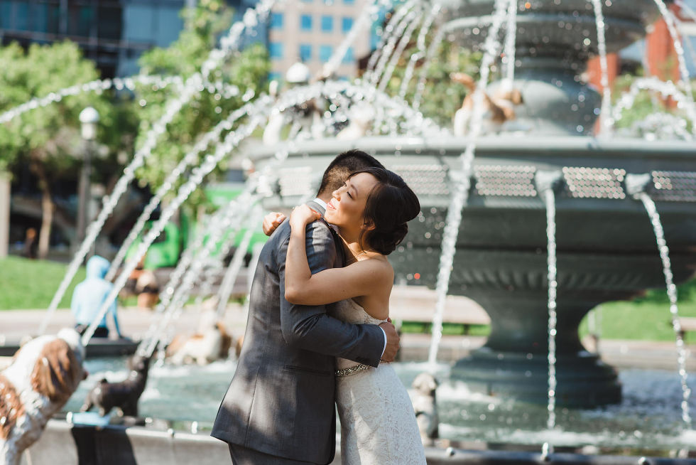 bride and groom hugging at the dog fountain in Berzcy Park, before their Parisian inspired wedding at La Maquette in Toronto Ontario