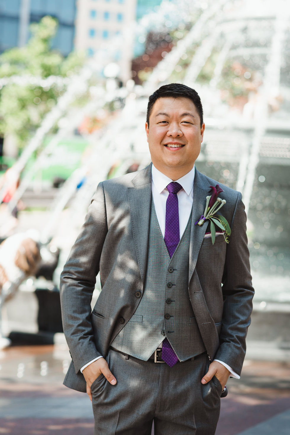 groom smiling at the dog fountain in Berzcy Park, before their Parisian inspired wedding at La Maquette in Toronto Ontario