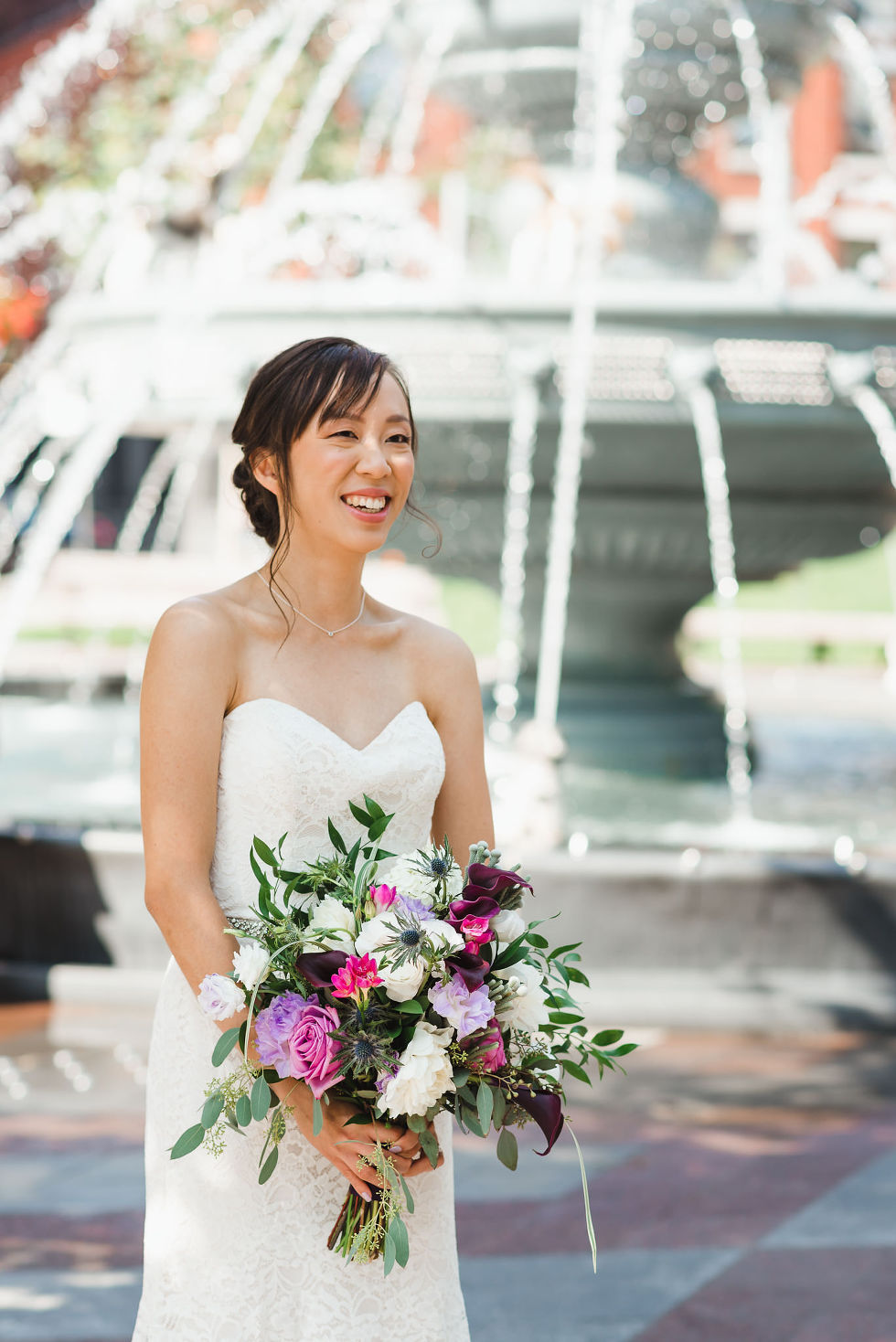 bride smiling at the dog fountain in Berzcy Park, before their Parisian inspired wedding at La Maquette in Toronto Ontario