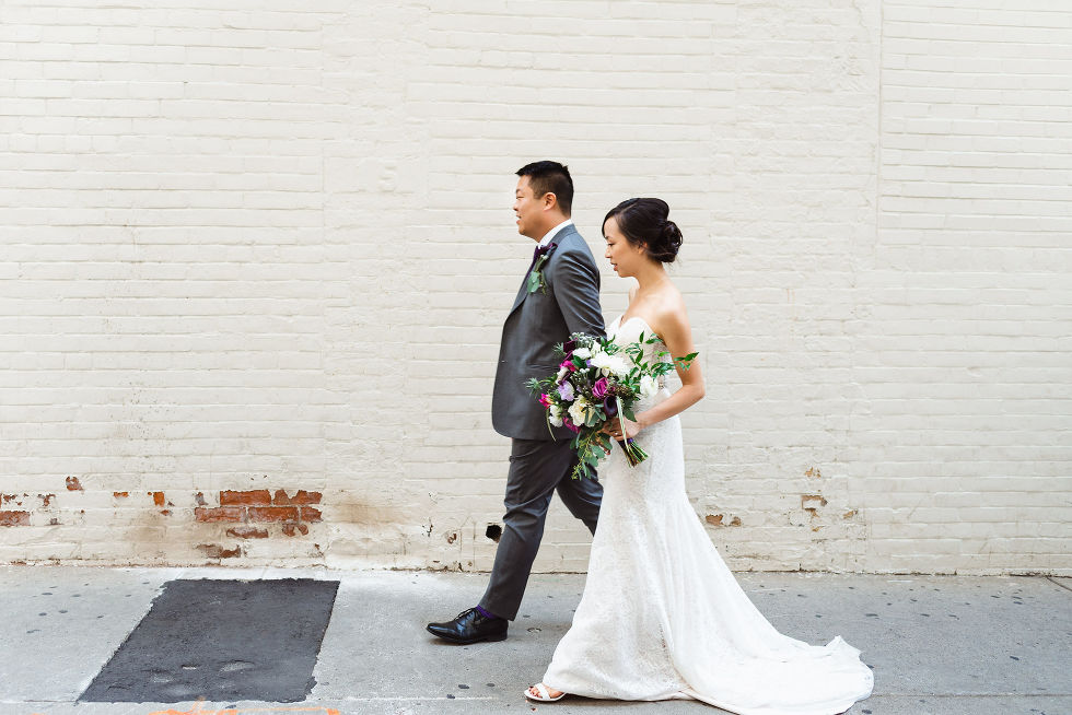 bride and groom walking hand in hand in front of white brick wall on their way to their Parisian inspired wedding at La Maquette in Toronto Ontario
